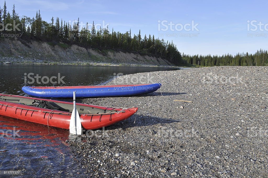 Inflatable kayaks on the shore taiga rivers. stock photo