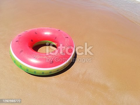 istock Inflatable pool funny life ring toy in shape of watermelon on the sand of the beach 1292593772