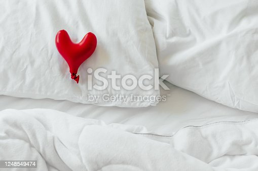 1078237178 istock photo Inflatable red heart on white bedding. 1248549474