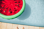 Top view of colorful inflatable watermelon floating mattress in a swimming pool on a summer day.