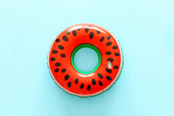 Inflatable watermelon ring over blue wooden background – zdjęcie