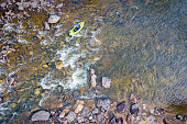 inflatable whitewater kayak below rapid on a mountain river (Poudre River in Colorado), aerial perspective