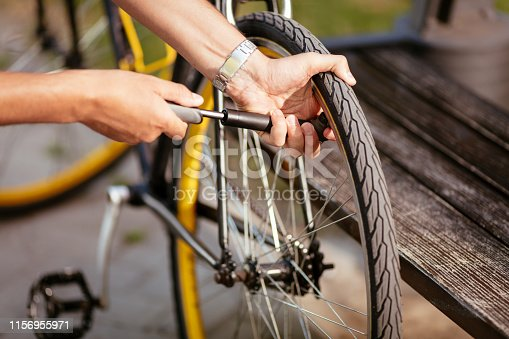 Close-up of a man pumping bicycle wheel on the street.