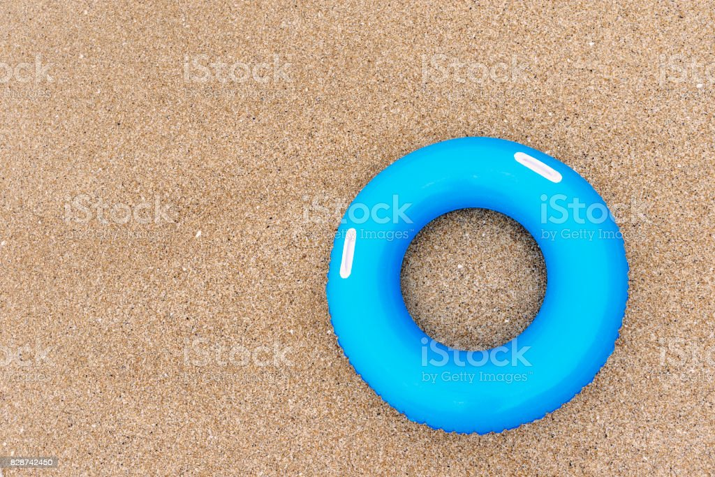 Inflated Blue rubber ring on sand from above. stock photo