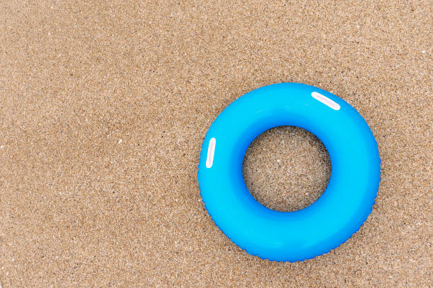 inflated blue rubber ring on sand from above. - rubber ring stock photos and pictures
