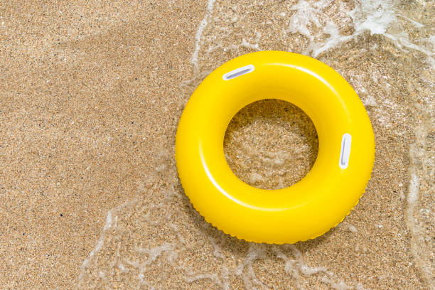 inflated yellow rubber ring on sand from above. - rubber ring stock pictures, royalty-free photos & images