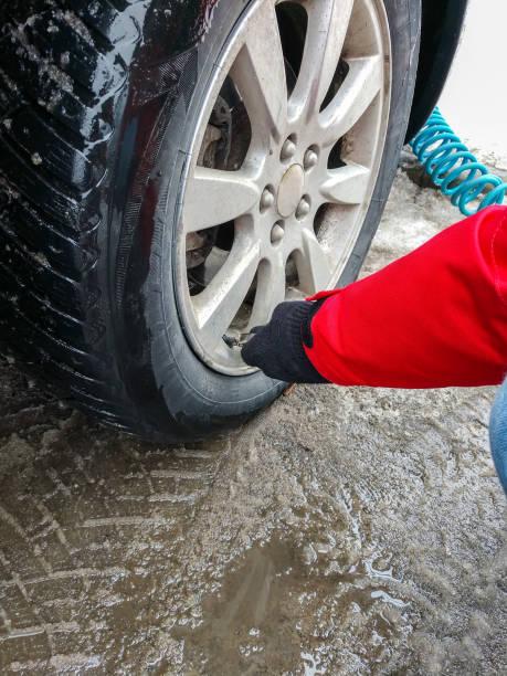 Gonfler les pneus de voiture en hiver avec une pompe à air - Photo