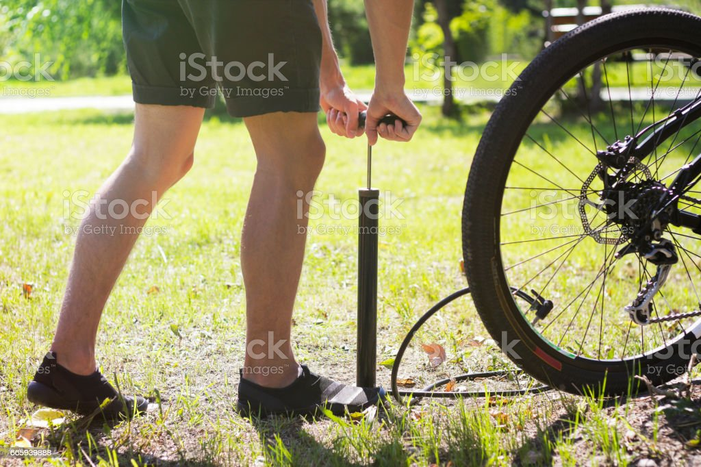 Inflating the tire of a bicycle. Cyclist repairs bike in forest. Bicyclist pumping air into the wheel. Biker uses a bicycle pump. Pumping air into an empty wheel of bike. foto stock royalty-free