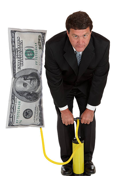 Inflation - Businessman Pumps Up Business stock photo