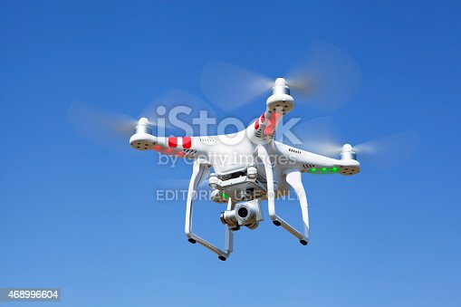 Rochester, Minnesota, USA - April 4, 2014: A DJI Phantom Vision 2+ quadcopter with camera in-flight against a blue sky.