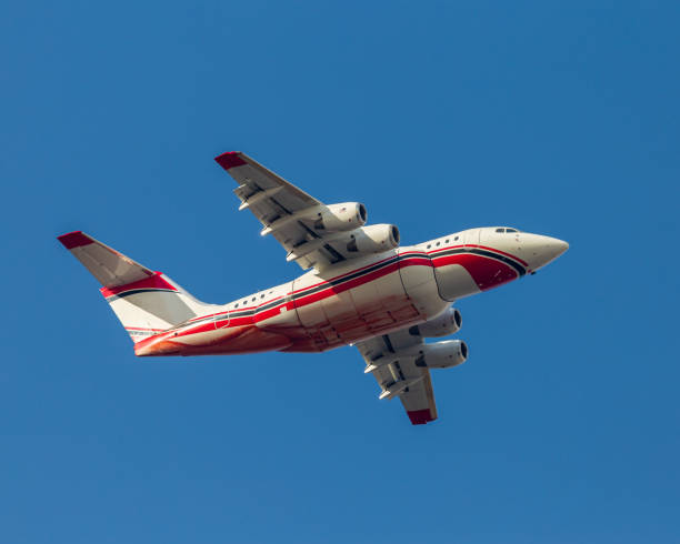 In-flight firefighting air tanker with retardant covering it's belly stock photo