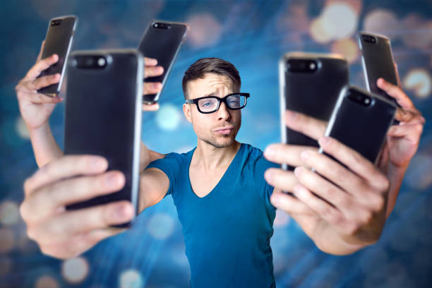 Influencer holding an exaggerated number of smartphones Young man with 6 arms is holding 6 smartphones to take a selfie. Abstract digital background with bokeh. puckering stock pictures, royalty-free photos & images