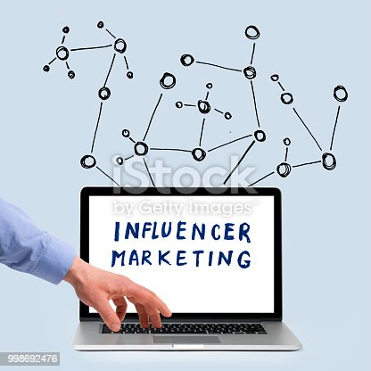 Hand touching laptop showing the words influencer marketing in front of network drawn on grey wall