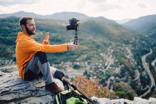 influencer tourist hiking and vlogging on the mountain top - vlogger stock photos and pictures