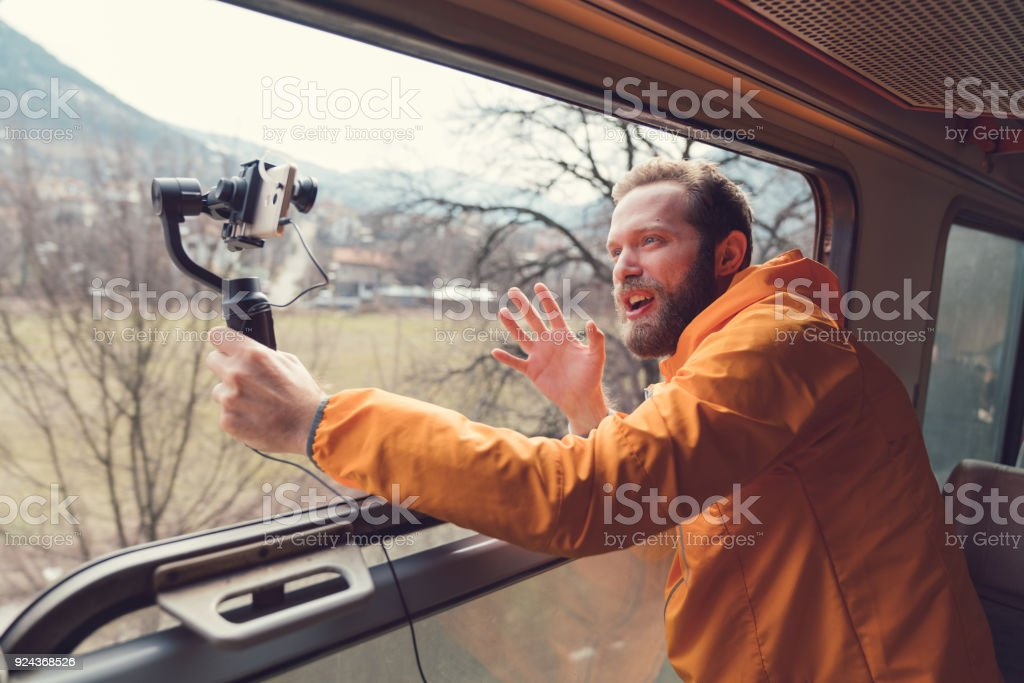 Influencer traveling in train and vlogging stock photo