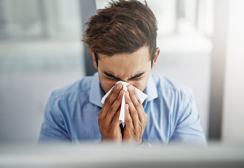 Shot of a young businessman blowing his nose with a tissue at work