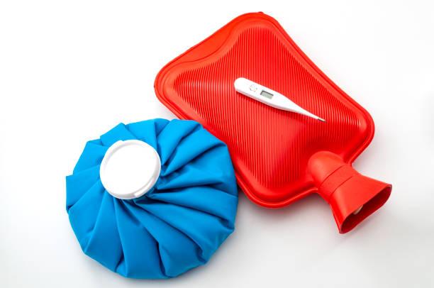 Idea conceptual de remedios tradicionales de gripe o gripe con paquete de hielo azul, botella de agua caliente de goma roja y termómetro aislado sobre fondo blanco - foto de stock