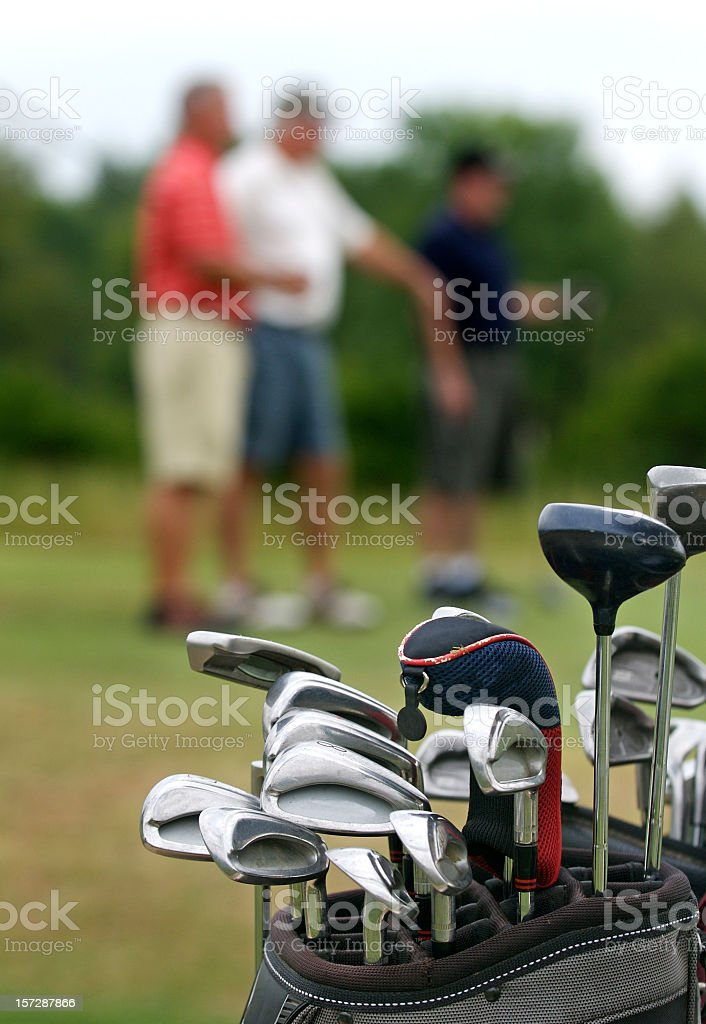 In-focus bag of golf clubs with out-of-focus golfers royalty-free stock photo