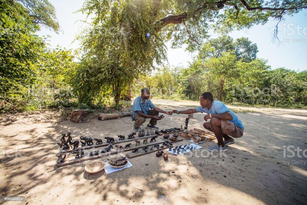 Informal Curios Business transaction under a tree stock photo
