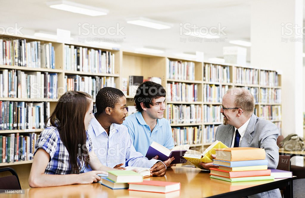 Informal seminar with three students and professor in library interacting royalty-free stock photo