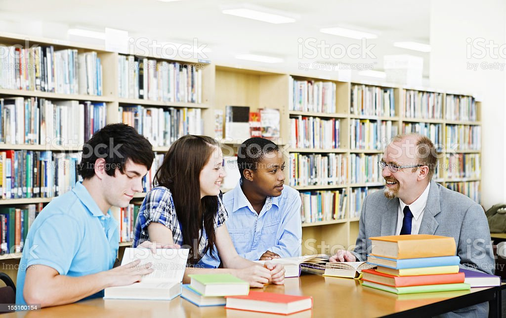 Informal seminar with three students and teacher in library royalty-free stock photo