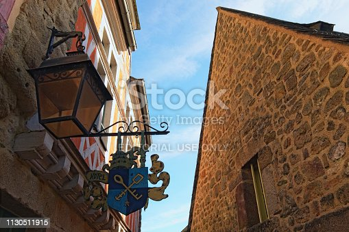 136699912 istock photo Information frame of the hotel (direction plate, ornate banner) with two keys. Beautiful traditional house in the town of Mont Saint Michel abbey at the background. Normandy, France, Europe 1130511915