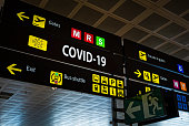 Information panel with Covid-19 word on it at an international airport, symbolizing the global spread of the coronavirus through global air traffic