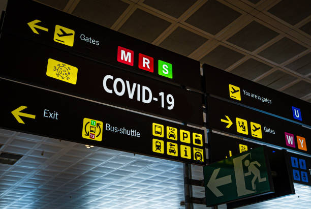 Information panel with Covid-19 word on it at an international airport. Information panel with Covid-19 word on it at an international airport, symbolizing the global spread of the coronavirus through global air traffic travel stock pictures, royalty-free photos & images