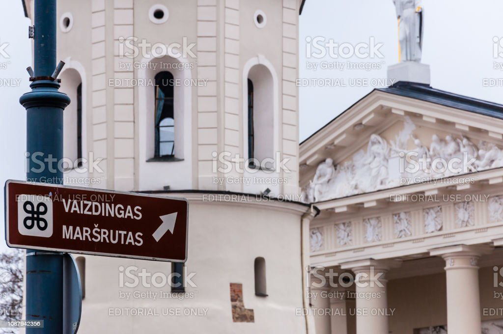 Information sign with scenic route title, Bell tower and the main facade fragment of The Cathedral Basilica of St Stanislaus and St Ladislaus of Vilnius. The main Roman Catholic Cathedral of Lithuania stock photo
