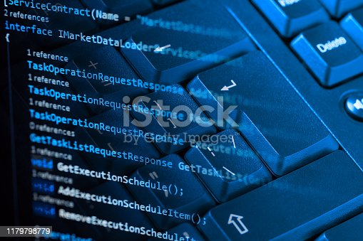 istock Information technology concept. Coding programmer language script text on screen monitor display with a PC keyboard. Programmer occupation job. Selective focus 1179798779