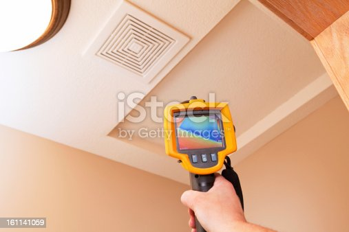 An infrared thermal imaging system being used during a home energy audit. The camera is pointed to an attic access hole showing a distinct blue (cold) area within the home's insulation. The center target area reads 50.7 degrees with a range of 45 to 72 degrees in the area.  Energy audits are performed to determine how efficient the house is and to suggest steps to increase energy efficiency.