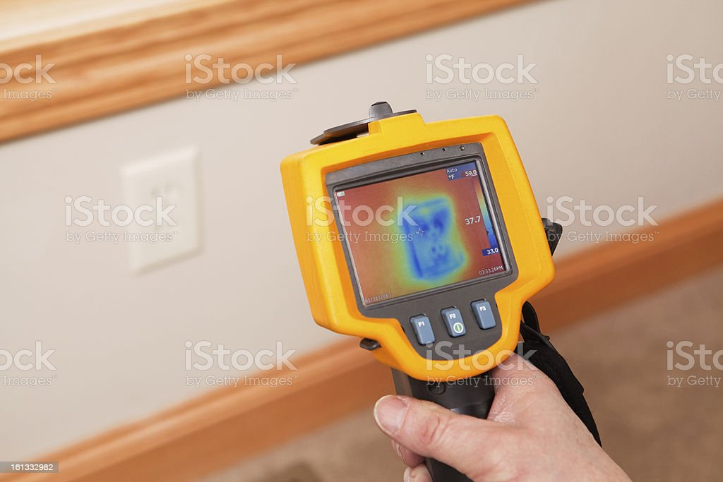 Infrared Thermal Imaging Camera Pointing to Wall Outlet stock photo