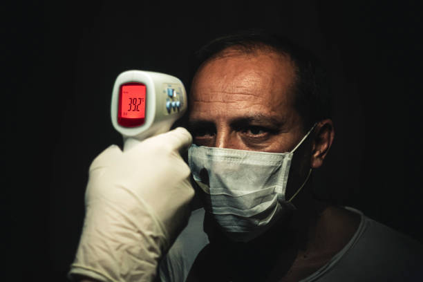 Infrared thermometer measuring a senior man's dangerously high body temperature stock photo