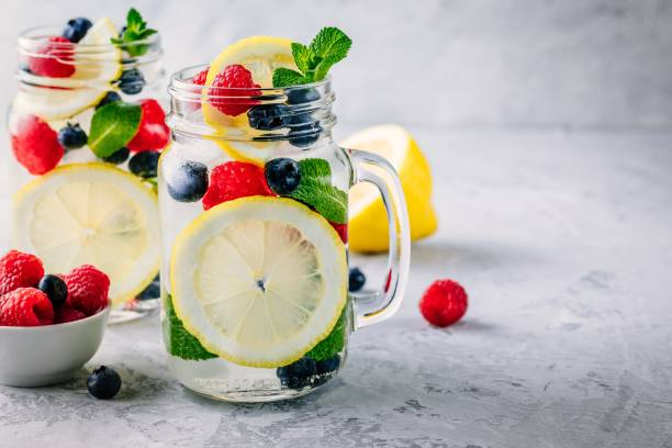 Infused detox water with lemon slice, raspberry, blueberry and mint. Ice cold summer cocktail or lemonade in mason jar Infused detox water with lemon slice, raspberry, blueberry and mint. Ice cold summer cocktail or lemonade in glass mason jar detox stock pictures, royalty-free photos & images