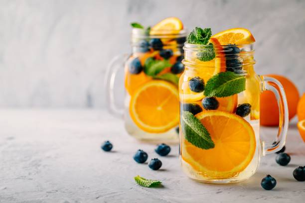 Infused detox water with orange, blueberry and mint. Ice cold summer cocktail or lemonade. stock photo