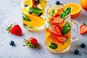 オレンジ、イチゴ、ブルーベリー、ミントを注入されたデトックス水。冷たい夏のカクテルやレモネードを氷します。