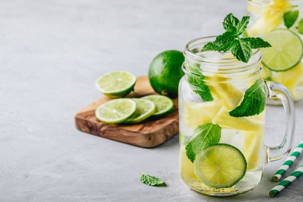 Infused detox water with pineapple, lime and mint. Ice cold summer cocktail or lemonade stock photo