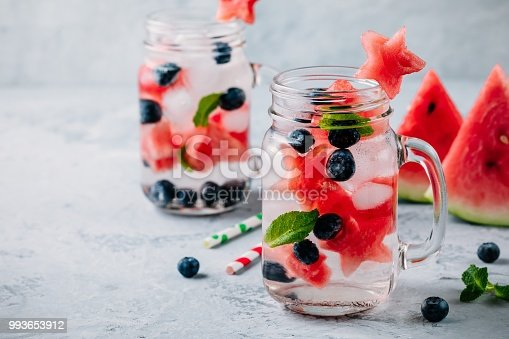 Infused detox water with watermelon, mint and blueberry. Ice cold summer cocktail or lemonade in glass mason jar