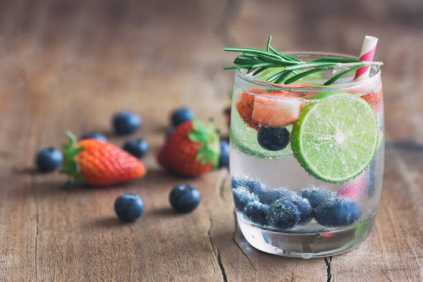 Infused water made from blueberry strawberry and lemon in sparkling mineral water look so freshness and healthy. Mixed fruit mojito on wood table with copy space. Summer refreshing drink concept. stock photo