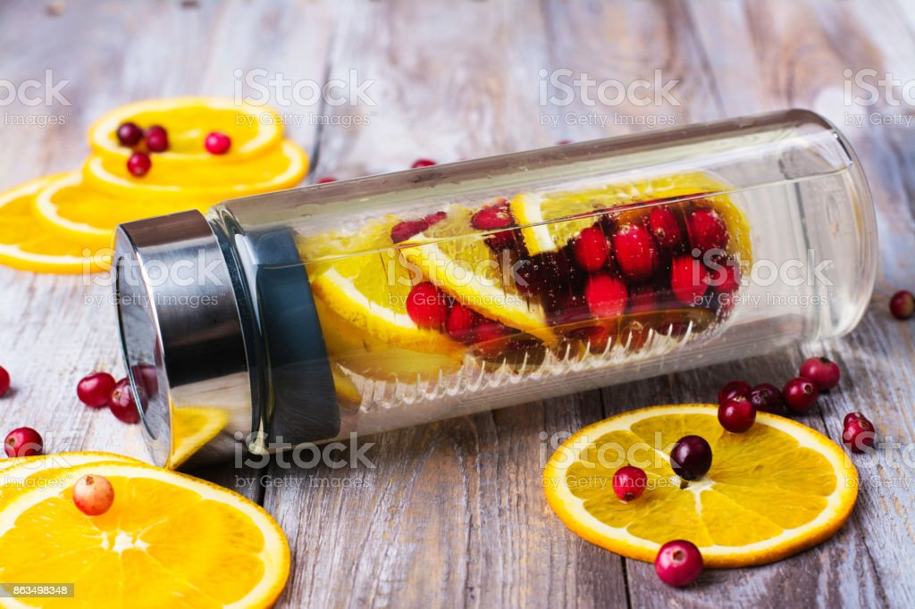 Infused water with cranberry and orange in a glass bottle stock photo