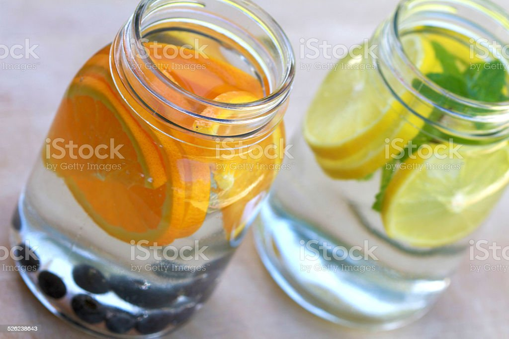 Infused water with orange and blueberry/lemon and mint stock photo