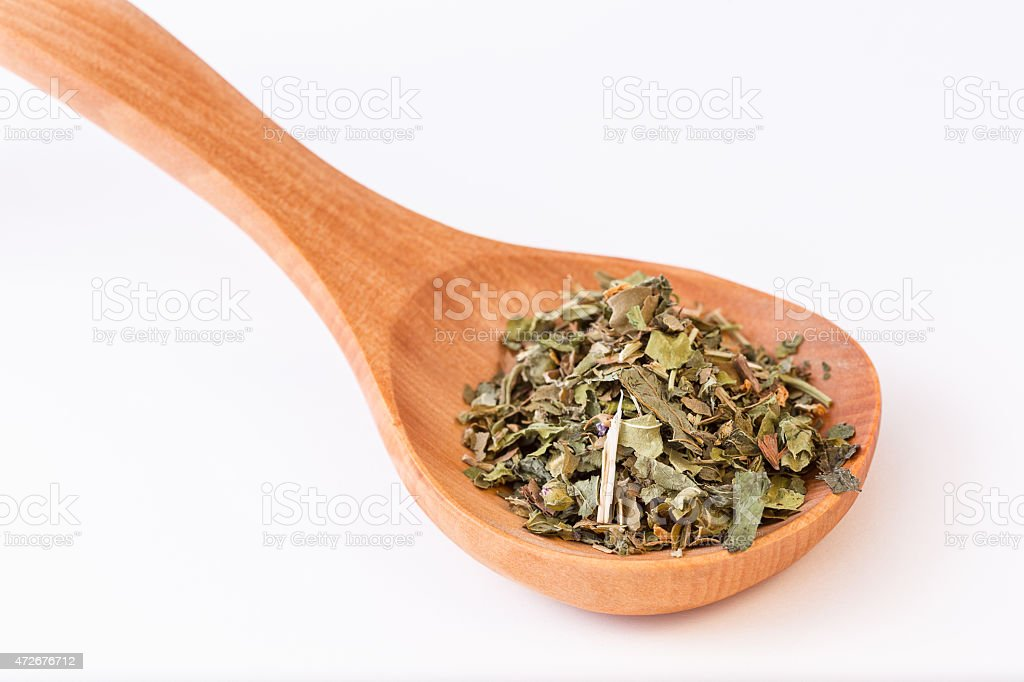 Infusion leaves in wooden spoon - spoon diagonally stock photo