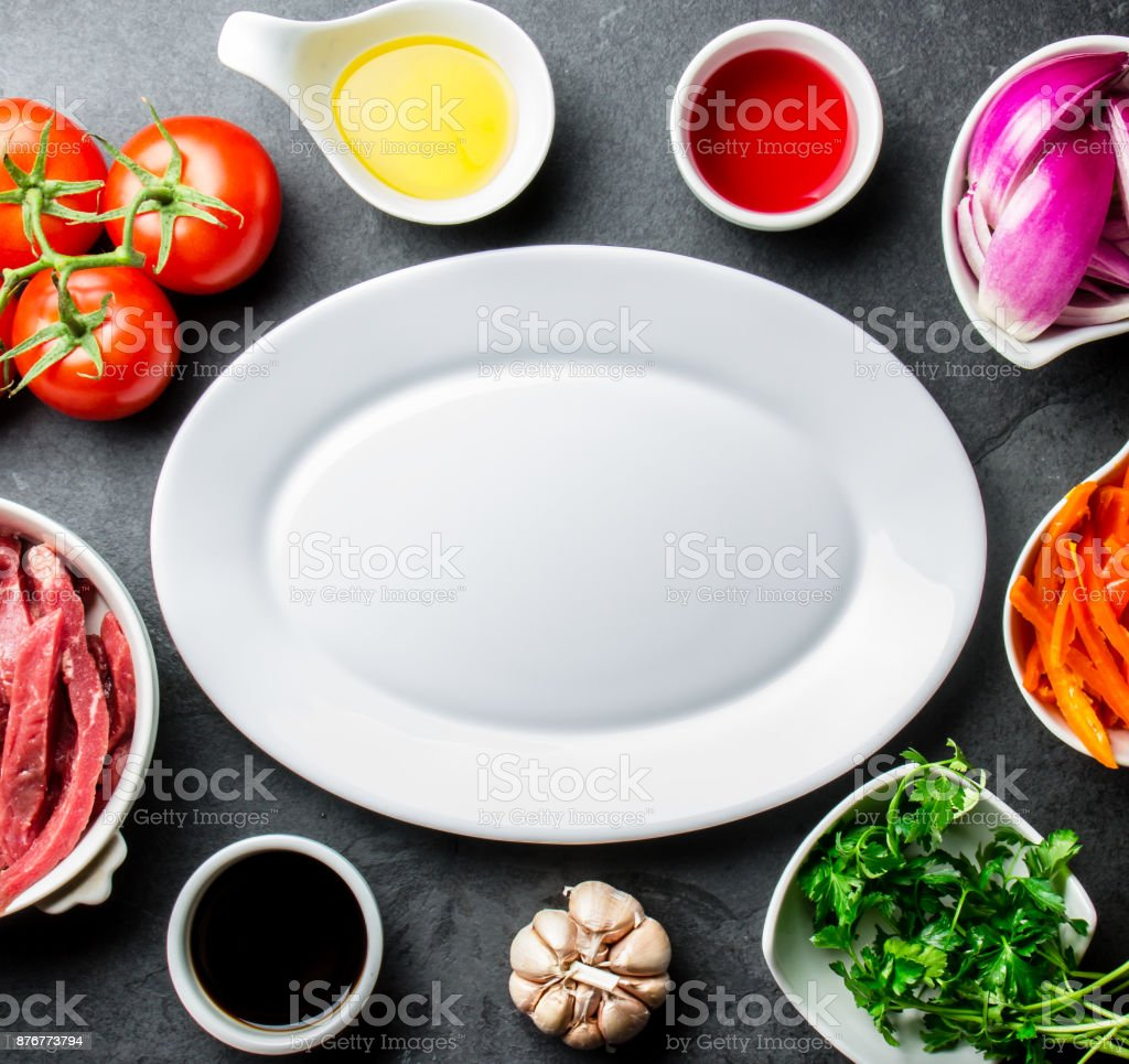 Ingredientes for cooking peruvian dish Lomo saltado - tenderloin beef, vegetables around white plate. Tot view stock photo
