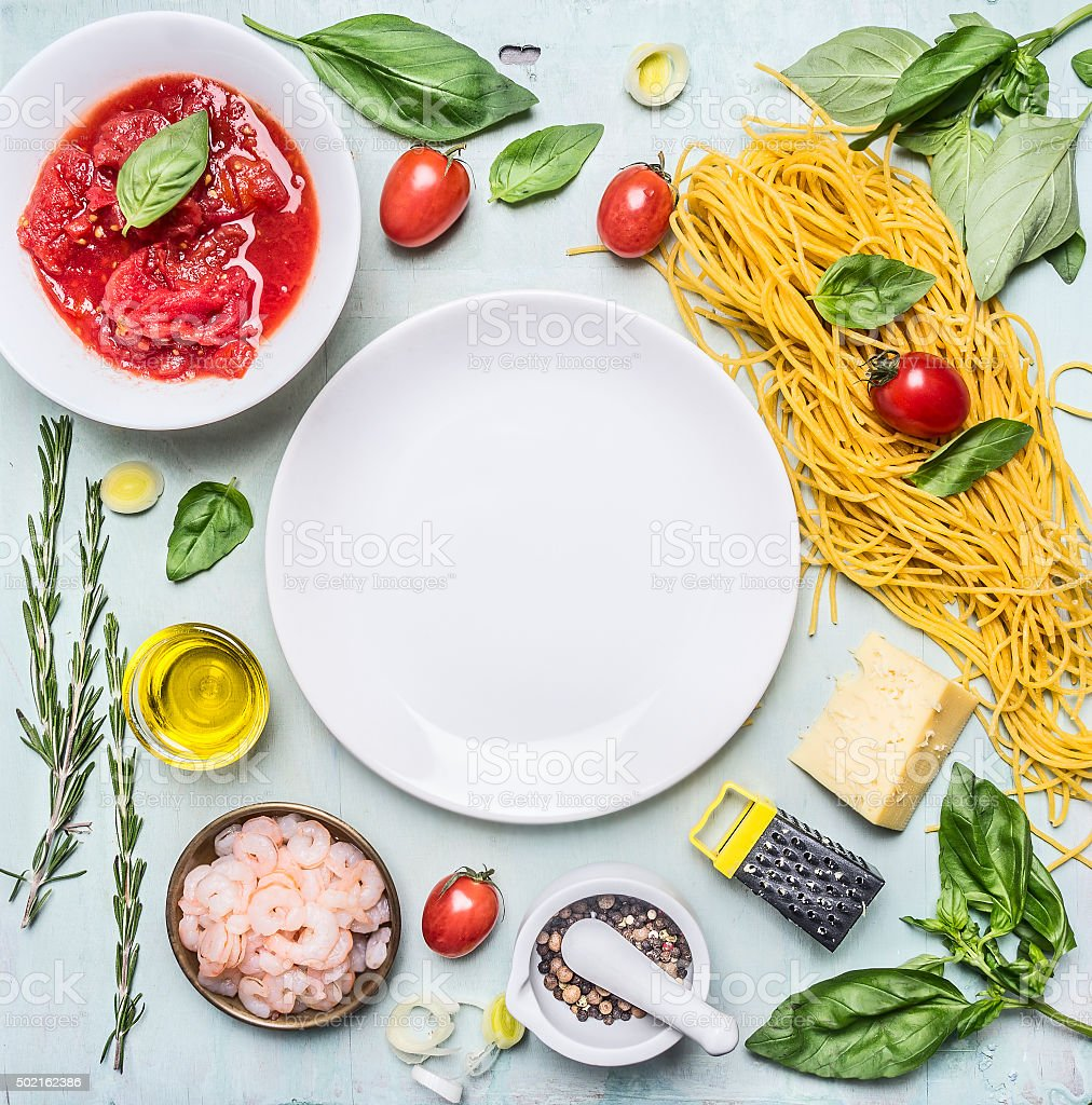 Ingredients cooking pasta,around  plate frame wooden background top view stock photo