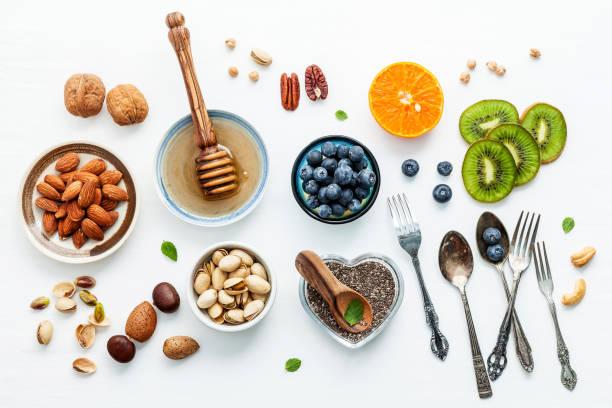 Zutaten für eine gesunde Lebensmittel Hintergrund, Nüssen, Honig, Beeren, Früchte, Heidelbeere, Orange, Mandeln, Walnüsse und Chia Samen. Das Konzept von gesunden Lebensmitteln auf weißem Hintergrund aus Holz eingerichtet. Flach zu legen. – Foto