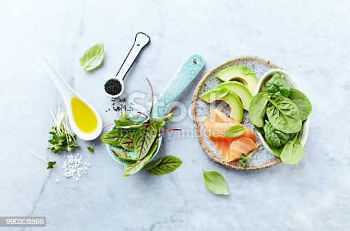 istock Ingredients for a healthy salad on gray stone background. Smoked salmon, avocado, spinach, sorrel, radis sprouts, black cumin. Flat lay. Healthy diet. Symbolic image. 990328566