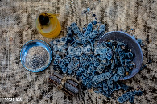 Ingredients for ayurvedic babool toothpaste on gunny bag's surface which are cinnamon stick, essential oil, baking soda, and babool powder.