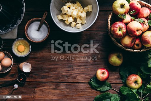 Directly above shot of a baking apple cake in kitchen. Butter in a bowl with fresh harvested apples, eggs and sugar on wooden table.