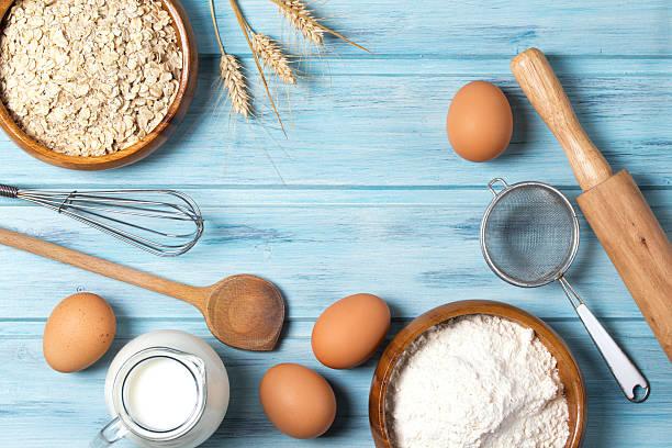 ingredients for baking, milk, eggs, wheat flour, oats and kitchenware - spitzenkekse stock-fotos und bilder