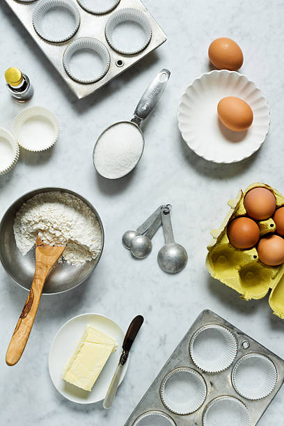 Ingredients For Baking Muffins or Cupcakes on Marble Countertop The ingredients for baking muffins or cupcakes are laid out on a marble countertop. This top down shot shows cupcake or muffin tins with papers, flour in a metal bowl with a wooden spoon, sugar in a measuring cup, vanilla, measuring spoons, a dish of butter with a knife, and a half dozen eggs. muffin tin stock pictures, royalty-free photos & images